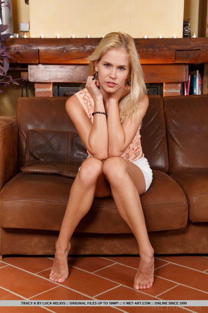 Молодая блондинка отдыхает на кожаном диване голышом
