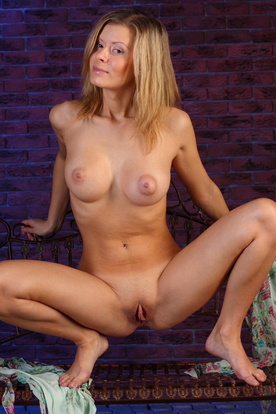 Сисястая блондинка Oliwia A демонстрирует прекрасную щелку своей киски перед камерой