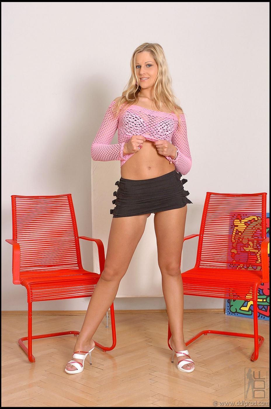 Вульгарная блондинка Sandra De Marco снимает свою сетчатую блузку и узкую юбку, а затем позирует обнаженной