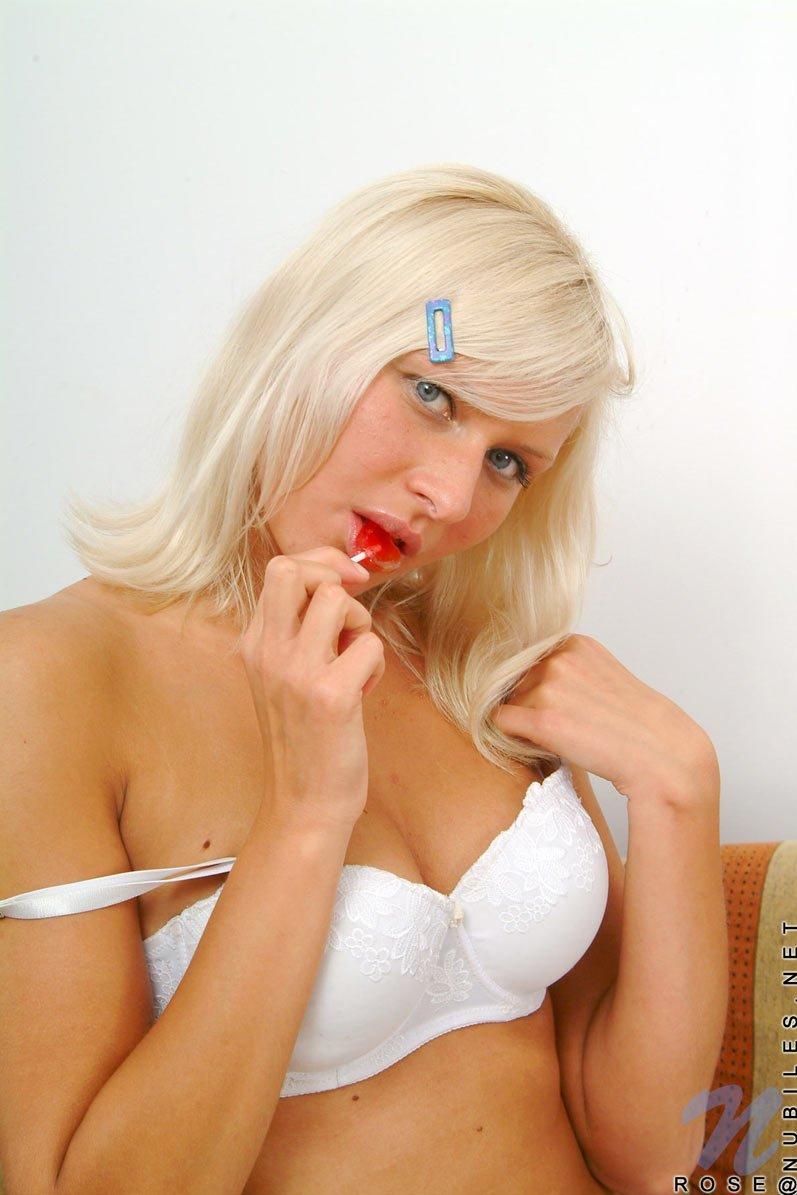 Забавная блондинка Rose Nubiles лижет леденец и раздевается, демонстрируя свое знойное тело