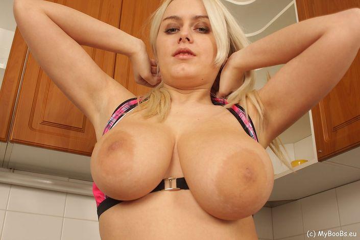 Соблазнительная блондинка с большой грудью мастурбирует пизду на кухне