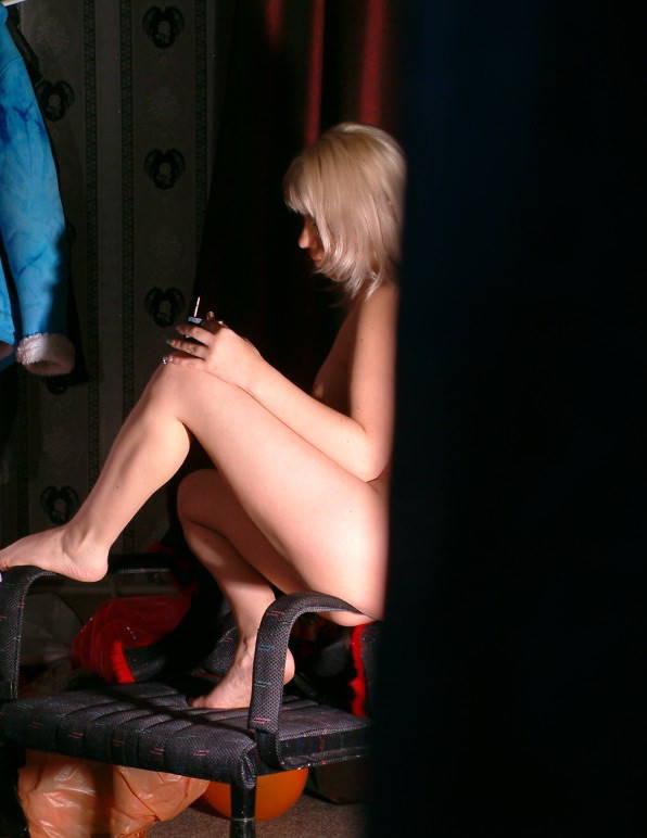 Голая девушка делает педикюр на стуле