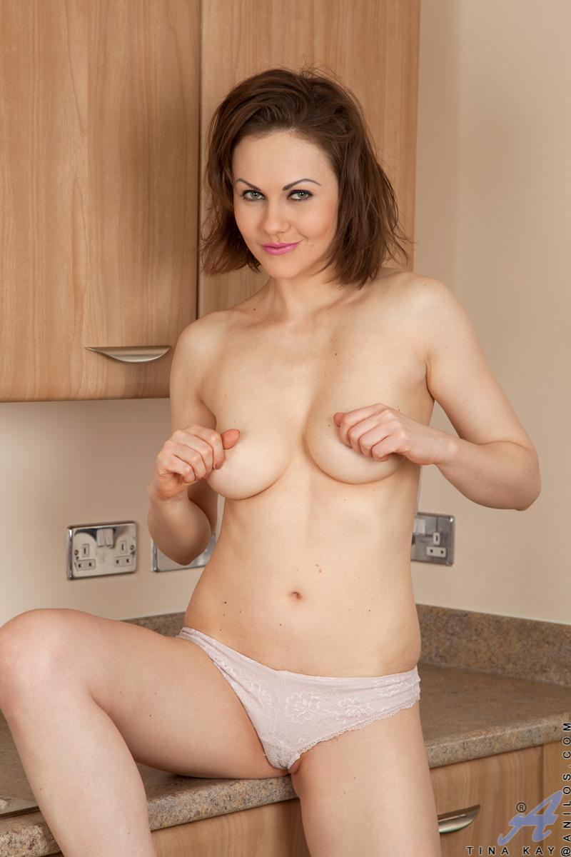 Извращенка Tina Kay сидит на кухне, мастурбируя и трогая свою грудь