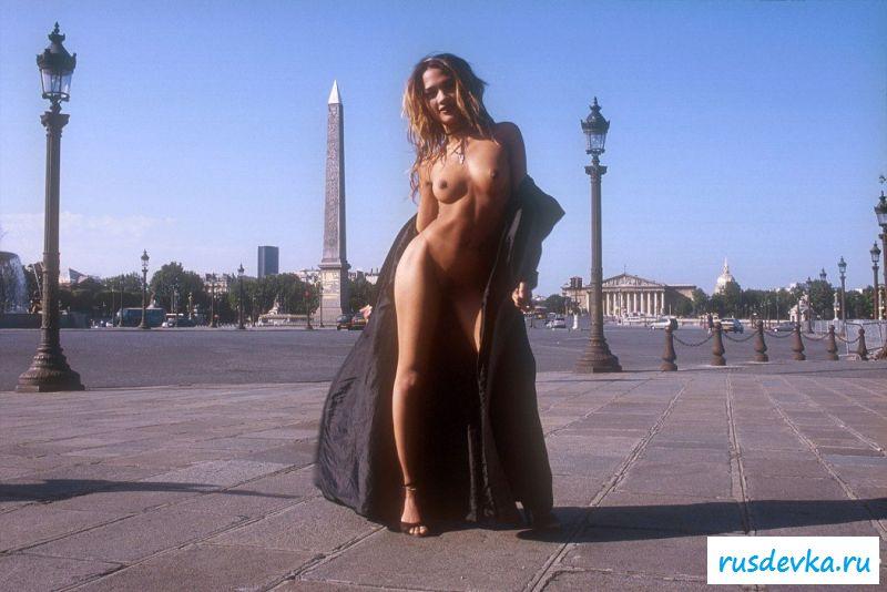 Эротичная женщина гуляет по городу и сбрасывает пальто