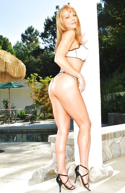 Взрослая блондинка с шикарными титьками позирует у бассейна
