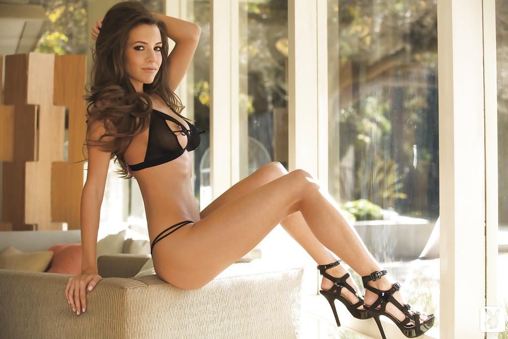 Кареглазая брюнетка показывает свое тело на замшевом диване
