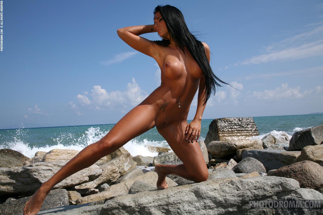 Сексуальная модель со стажем снимает свой влажный купальник на пляже