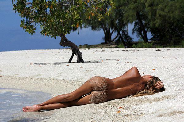 Стройная модель позирует голой на пляже