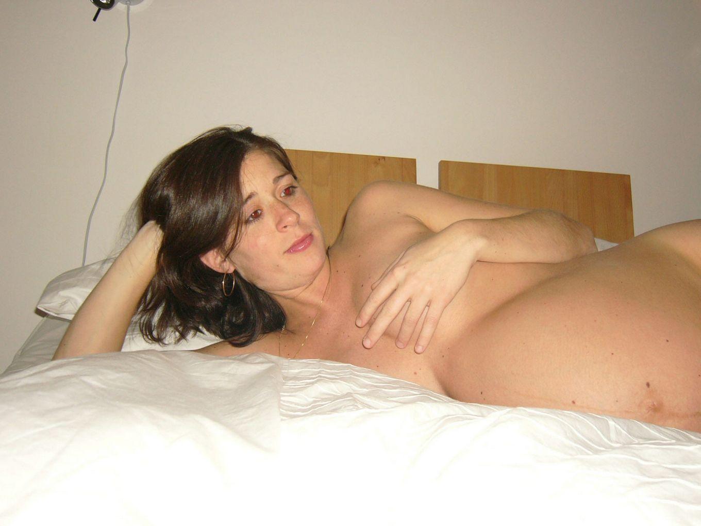 Беременная брюнетка лежит голая на кровати