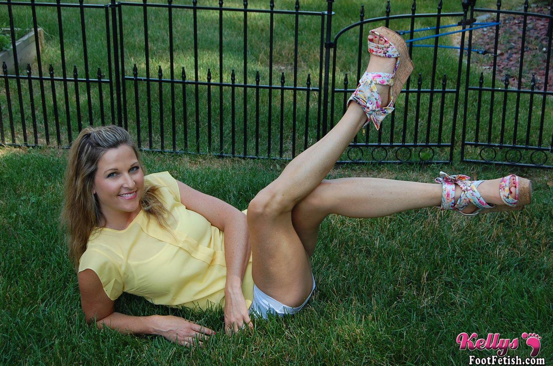 Домохозяйка показывает свои ступни сидя на газоне