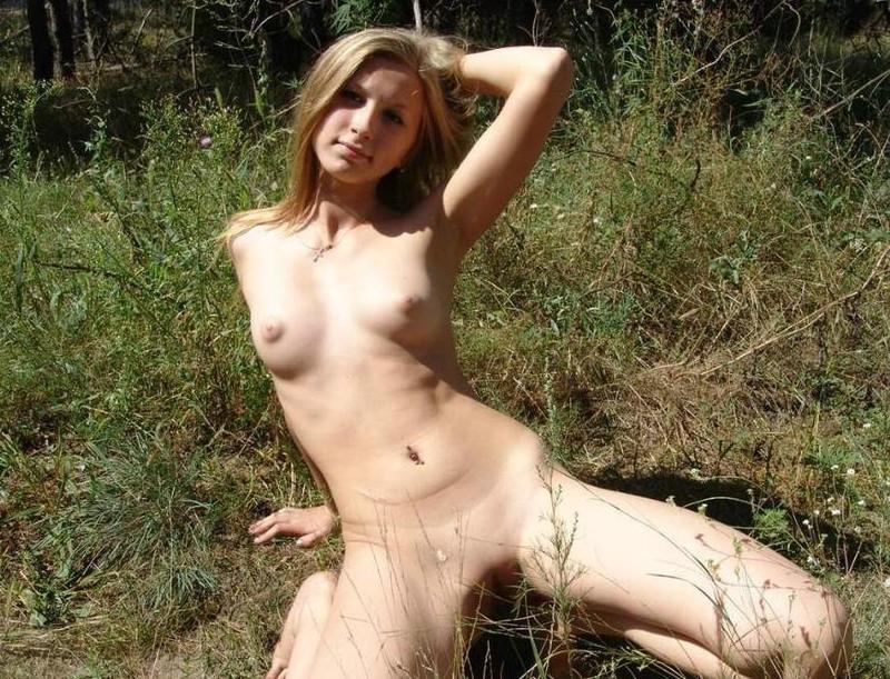 Голенькая девчонка валяется на траве и дрочит киску