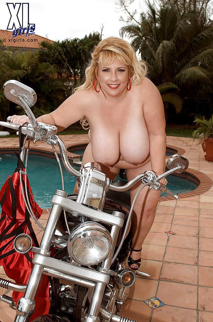 Жирная баба позирует и дрочит возле мотоцикла