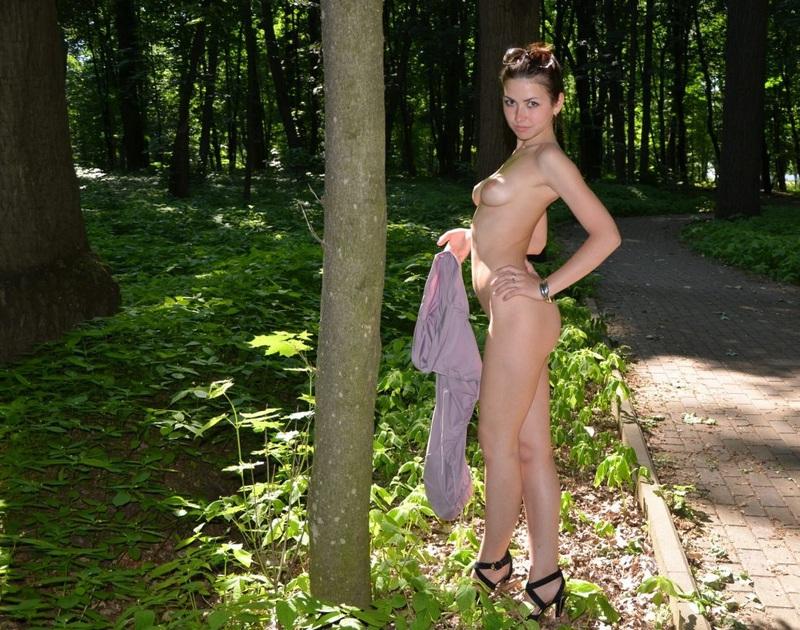 Голая девушка прогуливается в зеленом парке