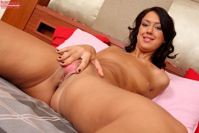 Сексуальная брюнетка мечтательно разлеглась голой на кровати