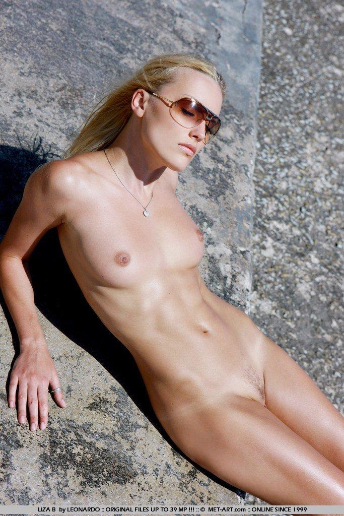 Блондинка Liza B с бритой киской и сексуальными крошечными сиськами раскрывает ноги на пляже