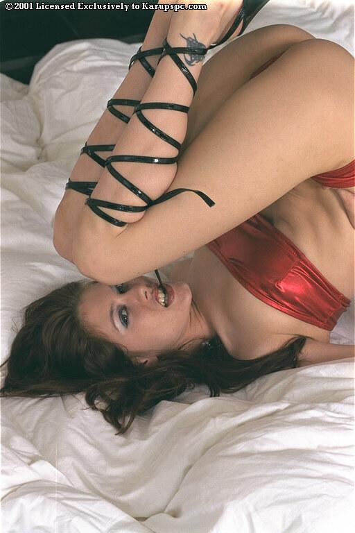 Брюнетка в красных трусах позирует на белоснежной кровати