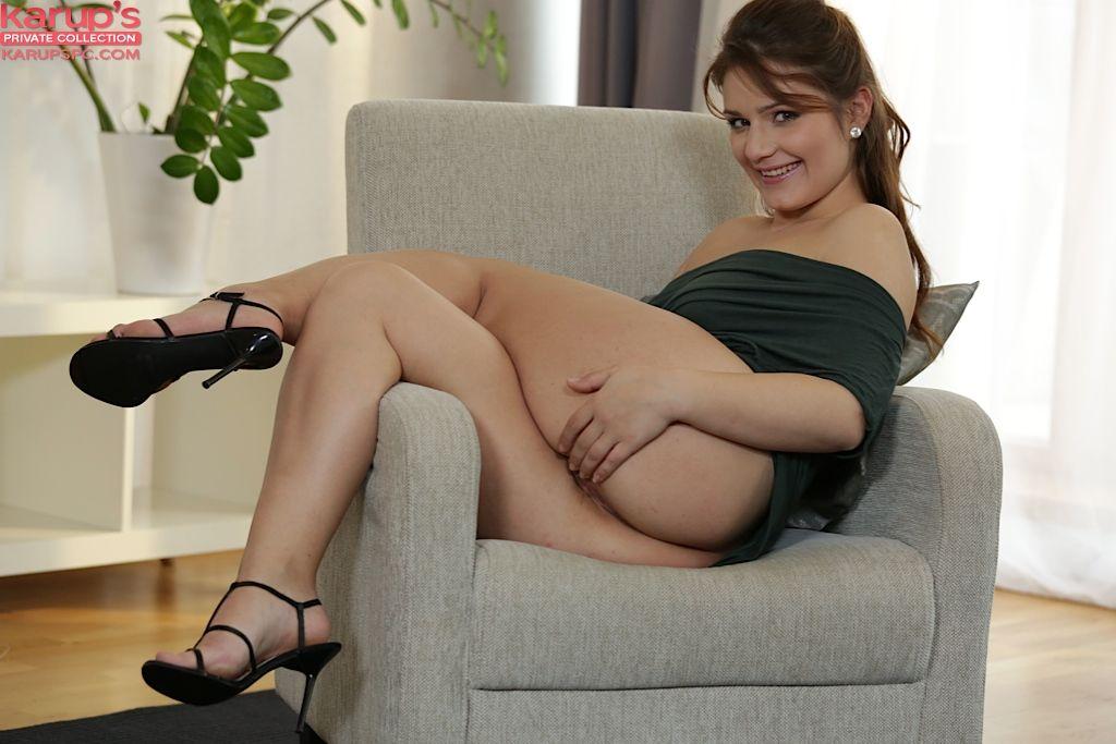Пышногрудая девка дрочит киску на кресле, не снимая платья и туфель