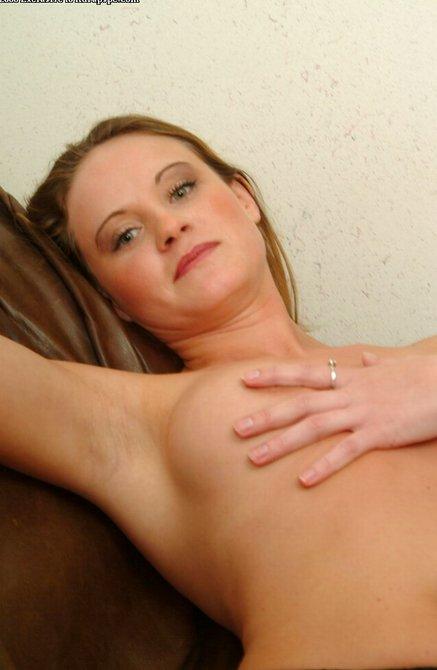 Симпатичная девушка с небритой киской на диване ласкается