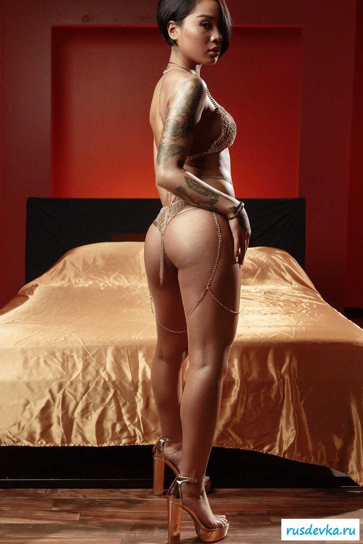 Обнаженная татуированная мулатка на большой кровати