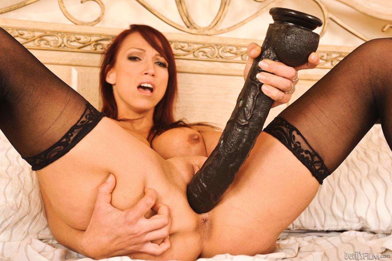Грудастая мамаша в чулках Nikki Hunter нетерпеливо трет киску двумя большими гигантскими игрушками