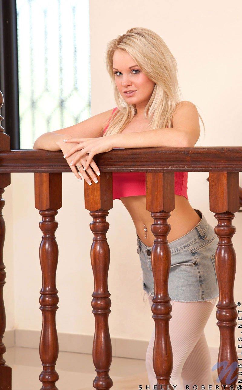 Милашка Shelly Roberts в розовом лифчике снимает колготки и показывает киску